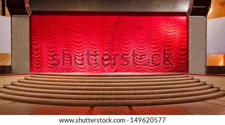 Theater stage with red curtains and steps. Theatrical scene,  the interior of the old theater of the luxury caribbean, tropical resort. Bahia Principe, Riviera Maya, Mexican Resort. - stock photo