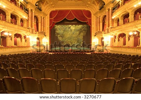 Theater stage with red velvet curtains and empty chairs in the foreground - stock photo