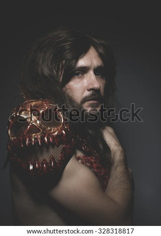 Theatrical, armored warrior king red skulls, long hair and intense look - stock photo