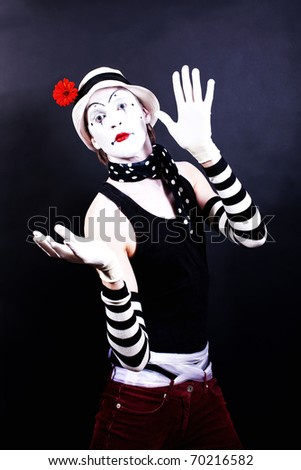 Theatrical mime in white hat with red flower on black background - stock photo