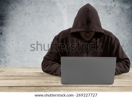 Theft. Hacker typing on a laptop with binary code in background - stock photo