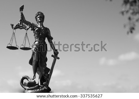 Themis, femida or justice goddess on bright blue sky copy space background. Black and white photography - stock photo