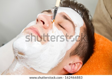 Therapist applying a face mask to a beautiful young man in a spa using a cosmetics brush  - stock photo