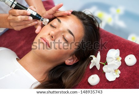 Therapist doing anti aging facial moisture infusion on woman. - stock photo
