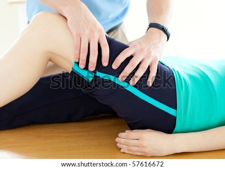 Therapist doing fitness exercises with a woman in gym - stock photo