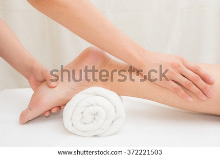 Therapist doing massage on woman leg in day spa - stock photo