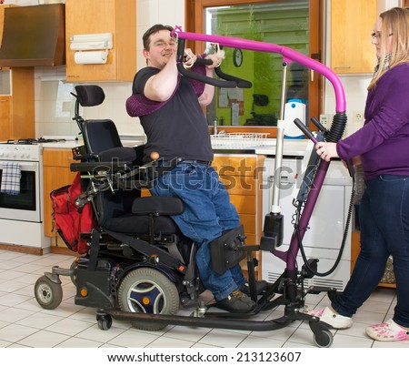 Therapist helping a spastic young man with infantile cerebral palsy caused by a complicated birth to maneuver himself into a multifunctional wheelchair with a patient lift - stock photo