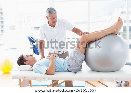 Therapist helping his patient with exercise ball in medical office - stock photo