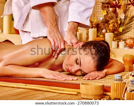 Therapist man giving Thai stretching massage to woman. Hands on neck. - stock photo
