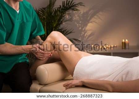 Therapist massaging female leg in massage room - stock photo