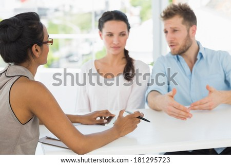 Therapist speaking with couple sitting at desk in therapists office - stock photo