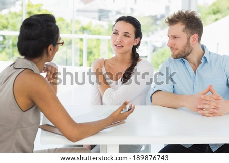 Therapist talking with couple sitting at desk in therapists office - stock photo
