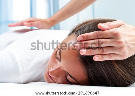 Therapists hands doing reiki therapy on girl. One hand on head and one hand on back. - stock photo