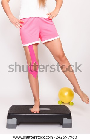 Therapy after knee injury with kinesio tape - stock photo
