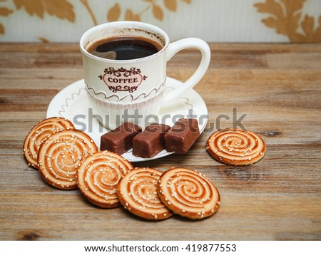 There are Cookies,Chocolate Candy, Porcelain Saucer and Cap with Coffe,Tasty Sweet Food on the Wooden Background - stock photo