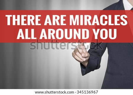 There Are Miracles All Around You word on virtual screen push by business woman red tab - stock photo