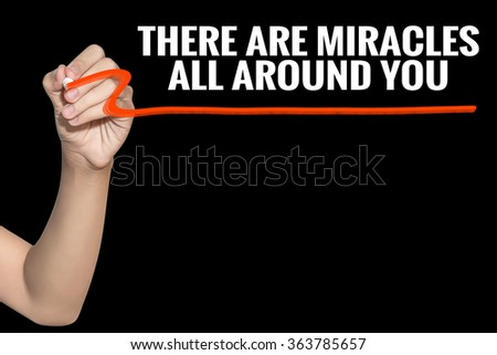 There Are Miracles All Around You word write on black background by woman hand holding highlighter pen - stock photo