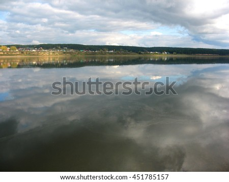 There are  river, cloudy  sky and homes on bank - stock photo