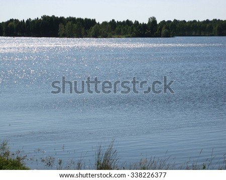 There are  river, sky, clouds and small trees - stock photo