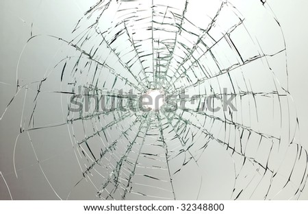 There is a broken car glass of windscreen with hole in picture center - stock photo