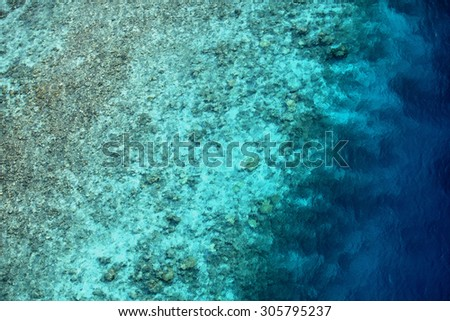 There is a lagoon where deep sea water is surrounded by coral and coral surrounded by deep sea water. Overlooking the edge of the lagoon from the sky, coral, shoal, deep sea.  - stock photo