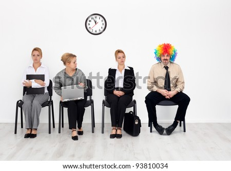There's one in every crowd - clown among job candidates waiting - stock photo