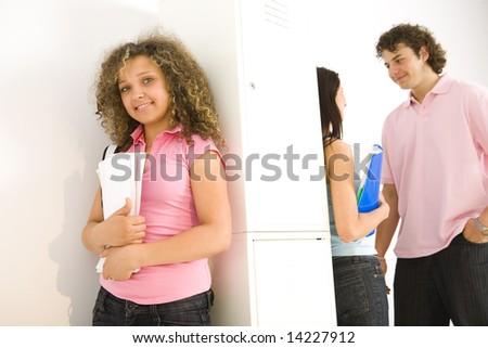 Theree schoolmate standing by school locker. Girls leaning for shool locker and holding notebooks. Boy talking with girl in blue shirt. Focuset on smiling girl in pink shirt. - stock photo