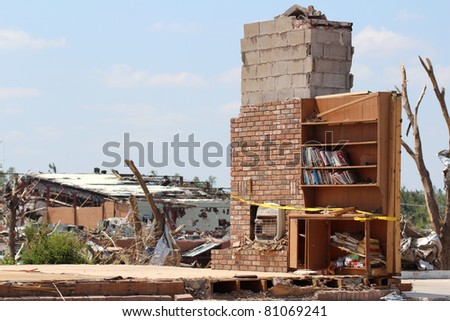 Theres nothing left but part of a chimney and a bookshelf with books intact after an EF-5 tornado destroyed thousands of homes and buisinesses and caused multi million dollars of damage in Joplin, Mo. - stock photo