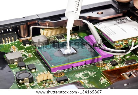 Thermal compound in syringe and laptop video chip - stock photo
