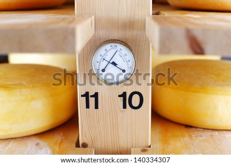 Thermometer and Hygrometer in a cheese cellar, allowing for correct temperature and humidity during the maturation of the cheese - stock photo