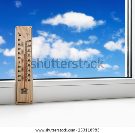 thermometer on the windowsill on a background of clouds in the sky - stock photo