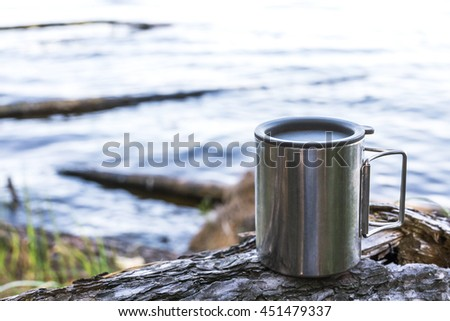 Thermos cup of coffee on wood with nature on background. Tourism and travel - stock photo