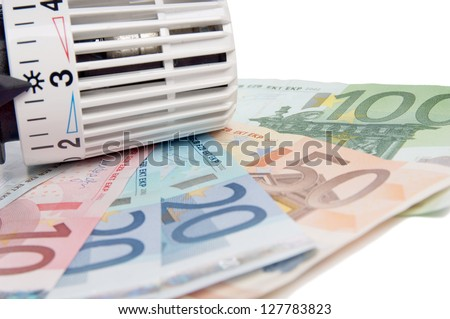 Thermostat with euro banknotes / heating costs - stock photo