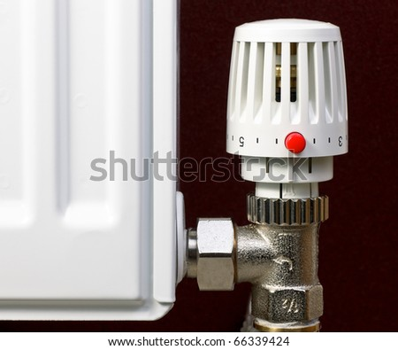 Thermostatic radiator valve with red economy button close-up - stock photo