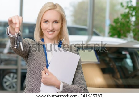 These are yours. Young female salesperson is offering car keys to a client after closing the deal. - stock photo