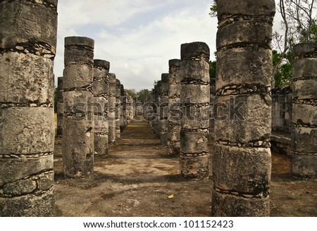 These columns surround the Temple of the Warriors, a massive temple structure in the ancient city of Chichen Itza. The columns continue on into the jungle where many are waiting for restoration. - stock photo