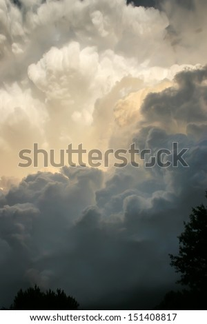These dark and dramatic thunderstorm clouds developed directly overhead on a hot, humid Kansas summer afternoon. You could sense the coming danger as a heavy storm and tornado warning soon followed. - stock photo