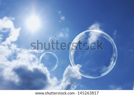 These soap bubbles floats calmly against a clear deep blue sky and clouds representing natural 'Thought Bubbles' on possible ideas for clean atmosphere, fresh air and a green environment. - stock photo