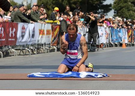 THESSALONIKI, GREECE - APRIL 21:Greek marathon runner SASAKAROS KONSTANTINOS worship the Greek flag on the finnish line on 8th Marathon Alexander the Great on April 21,2013 in Thessaloniki, Greece - stock photo