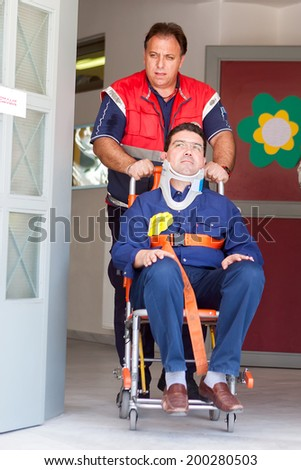 THESSALONIKI, GREECE- APRIL 24, 2013: Paramedic assisting injured teacher, exiting the building, during an earthquake exercise at 6th primary school in Thessaloniki, Greece. - stock photo