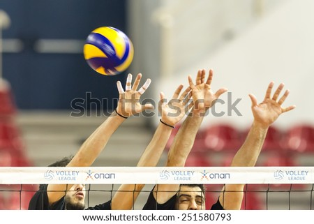 THESSALONIKI, GREECE - FEBRUARY 5, 2015 : Players in action on the net during the Hellenic Volleyball League game Paok vs Aris at PAOK Sports Arena. - stock photo