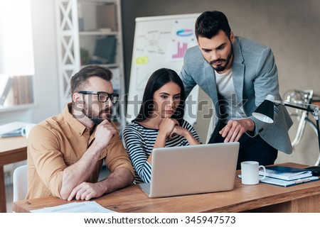 They need an expert advice. Group of confident business people in smart casual wear looking at the laptop together - stock photo