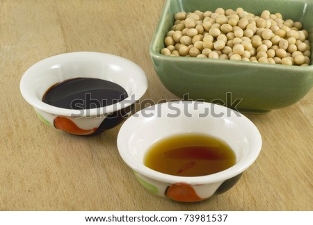 Thick and light soy sauce in ceramic dish and soy beans in green porcelain bowl. - stock photo