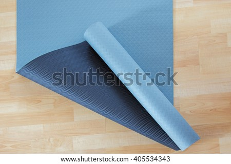 Thick anti slip blue and black fitness yoga practice or meditation mat made of PVC on yellow laminate wooden floor - stock photo
