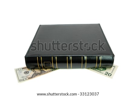 Thick black book with golden trimming presses down twenty dollar bills isolated - stock photo