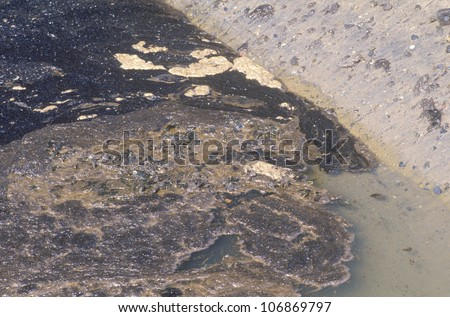 Thick, black oil covering the water along the shoreline of Huntington Beach after a spill off the coast of Orange County, California - stock photo