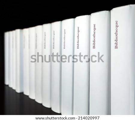 Thick books stacked in a row on a wooden shelf - stock photo