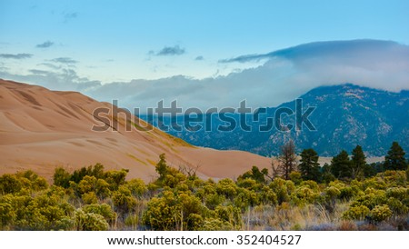 Thick clouds at Sunrise over the sangre de cristo mountains and the great sand dunes - stock photo