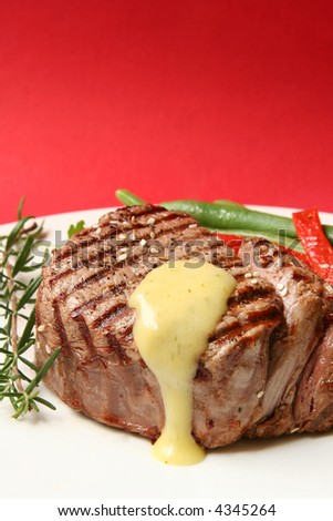 Thick filet mignon with bearnaise sauce, green beans and red peppers, and a sprig of rosemary.  Red background. - stock photo