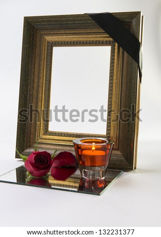 thick gold frame with sympathy rose and candlelight - stock photo